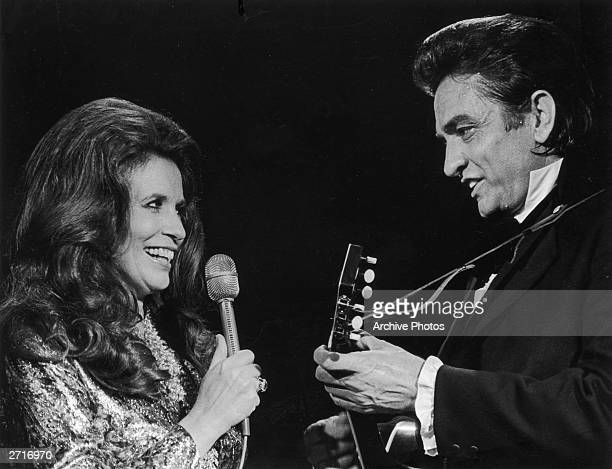 Married country singers Johnny Cash and June Carter Cash perform a duet on stage