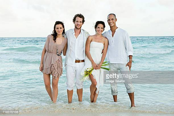 Married couple and friends paddling in sea