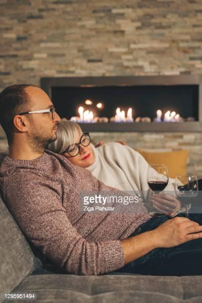 echtpaar dat thuis op oudejaarsavond knuffelt - 30 39 years stockfoto's en -beelden