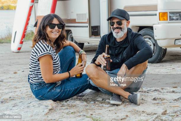 married couple drinking beer outside of a campervan - stock photo - camper van stock pictures, royalty-free photos & images