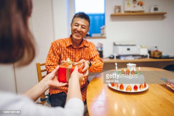 家で誕生日パーティーを持っている結婚されていたカップル - 記念日 ストックフォトと画像