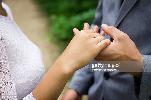 Married couple holding hands, showing wedding ring