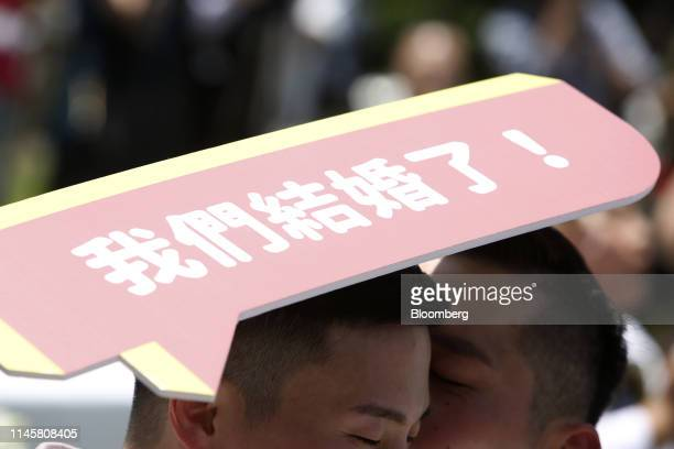 """Married couple holds a a sign reading """"We Are Married!"""" during a pro same-sex marriage party organized by the Taipei City government and Marriage..."""