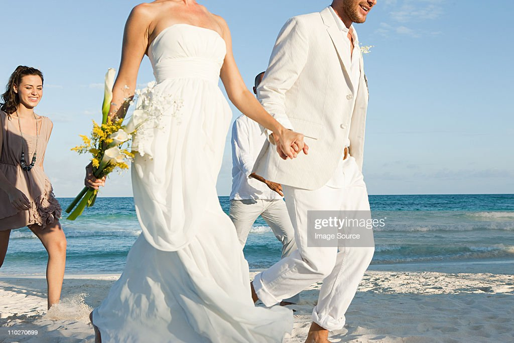 Married couple on beach with friends : Stock Photo