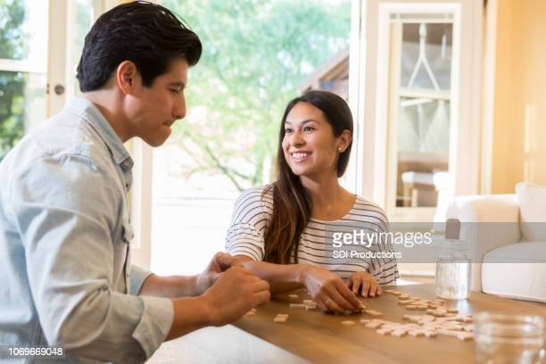 Married couple organize strategize during word game at home