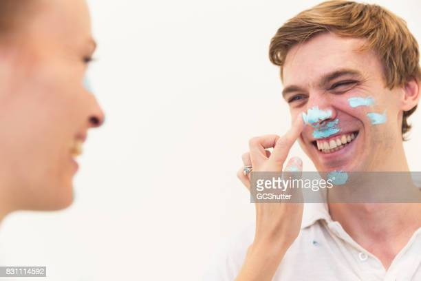 Married couple playfully painting each other's faces