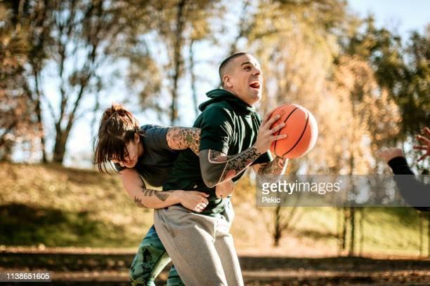 married couple playing basketball outdoor - homem pegando mulher imagens e fotografias de stock