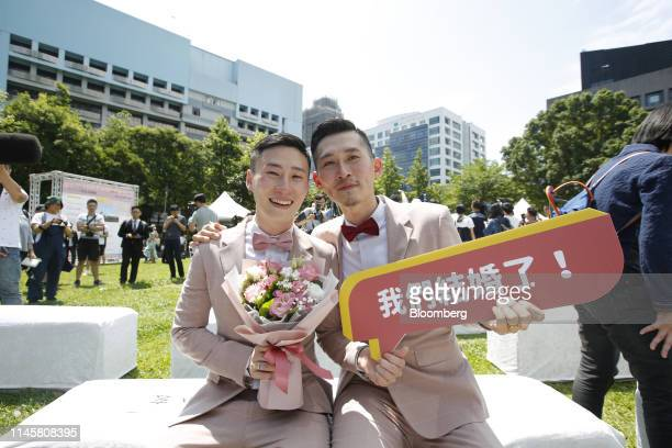 """Married couple poses for photographs with a sign saying """"We Are Married!"""" during a pro same-sex marriage party organized by the Taipei City..."""
