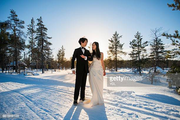 A married couple stand at snow field.