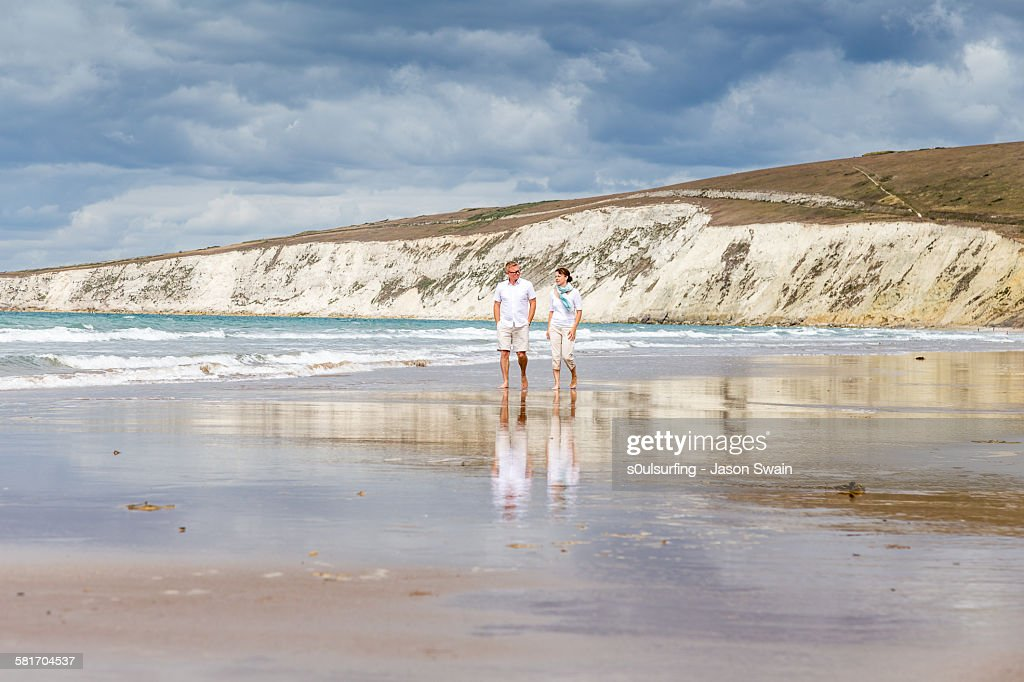 Married couple walking along the beach : Stock Photo