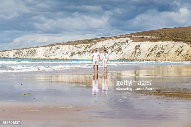 married couple walking along the beach - s0ulsurfing stock pictures, royalty-free photos & images