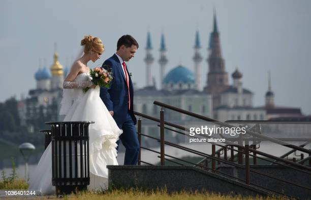 A married couple walks past a backdrop of the Qol Sharif mosque in the city of Kazan Russia 11 July 2015 Photo Marcus Brandt/dpa | usage worldwide