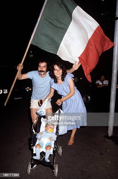 A married couple with their baby in a stroller wearing light blue dresses are waving the Italian flag to celebrate the many wins of the Italy...