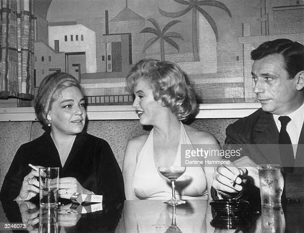 Married French actors Simone Signoret and Yves Montand flank American actor Marilyn Monroe while having cocktails in a booth at 20th Century Fox...