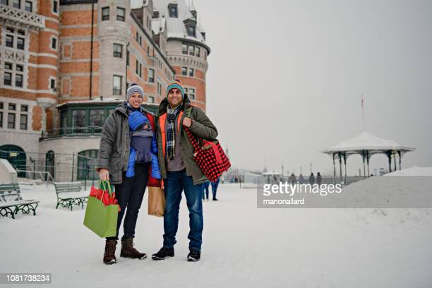 married gay couple shopping for christmas holiday with their baby - chateau frontenac hotel stock pictures, royalty-free photos & images