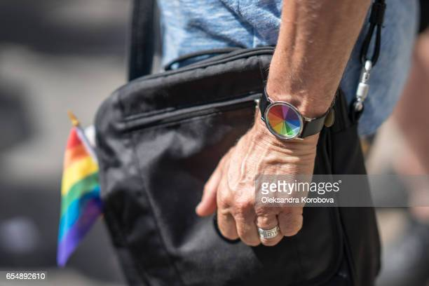 married man in the crowd wearing colorful rainbow watch and a flag. - istock photo stock pictures, royalty-free photos & images