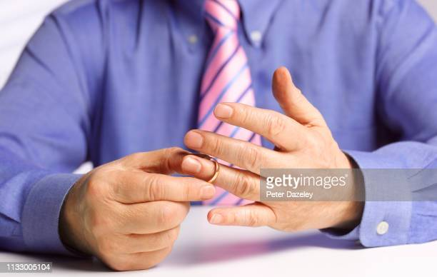 married man removing wedding ring prior to starting an affair - absence stock pictures, royalty-free photos & images