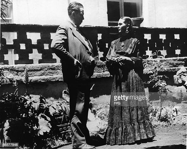 Married Mexican painters Diego Rivera and Frida Kahlo talk together in the garden near the porch of Kahlo's home Mexico City Mexico 1937