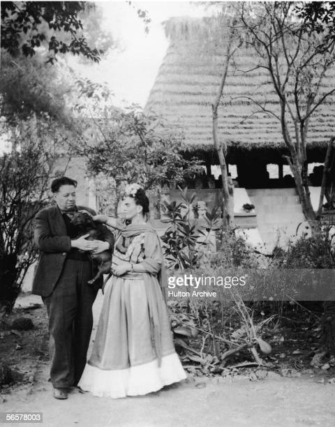 Married Mexican painters Frida Kahlo and Diego Rivera stand together with a pet dog in front of thatchtedroof hut which houses a number of...