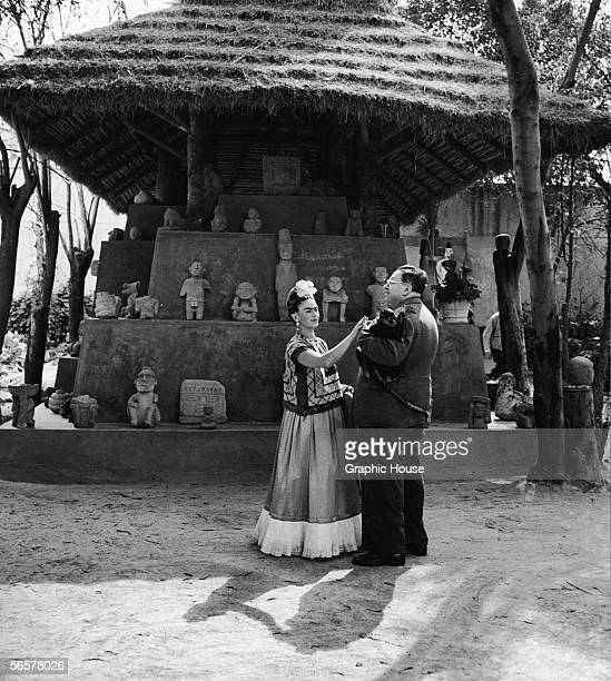 Married Mexican painters Frida Kahlo and Diego Rivera stand together with a pet monkey in front of thatchtedroof hut which houses a number of...