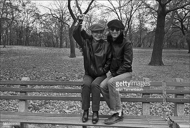 Married musicians John Lennon and Yoko Ono both in leather jackets and berets raise an arm and smile as they sit on a bench in Central Park New York...