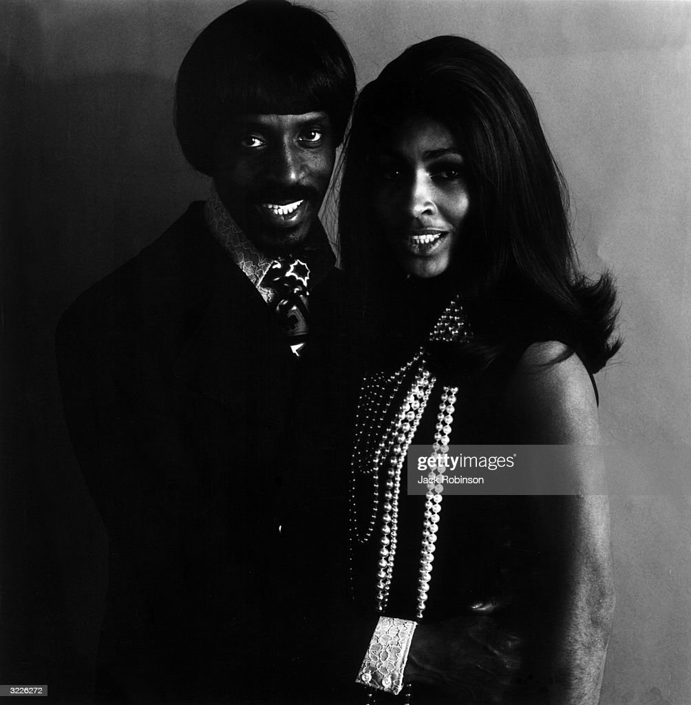 Studio portrait of married musical duo Ike and Tina Turner, with Ike holding Tina around her waist.