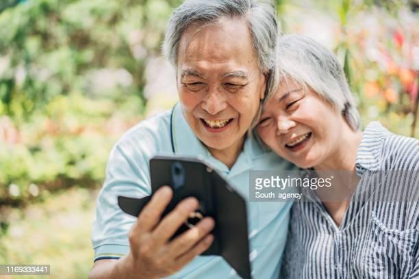 getrouwd senior paar met behulp van smart phone in park - aziatische etniciteit stockfoto's en -beelden