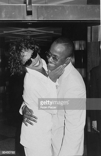 Married singer Whitney Houston and Bobby Brown wearing sunglasses and hugging after her concert