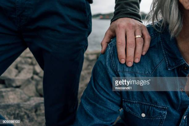 married son putting hand on father's shoulder - sostegno morale foto e immagini stock