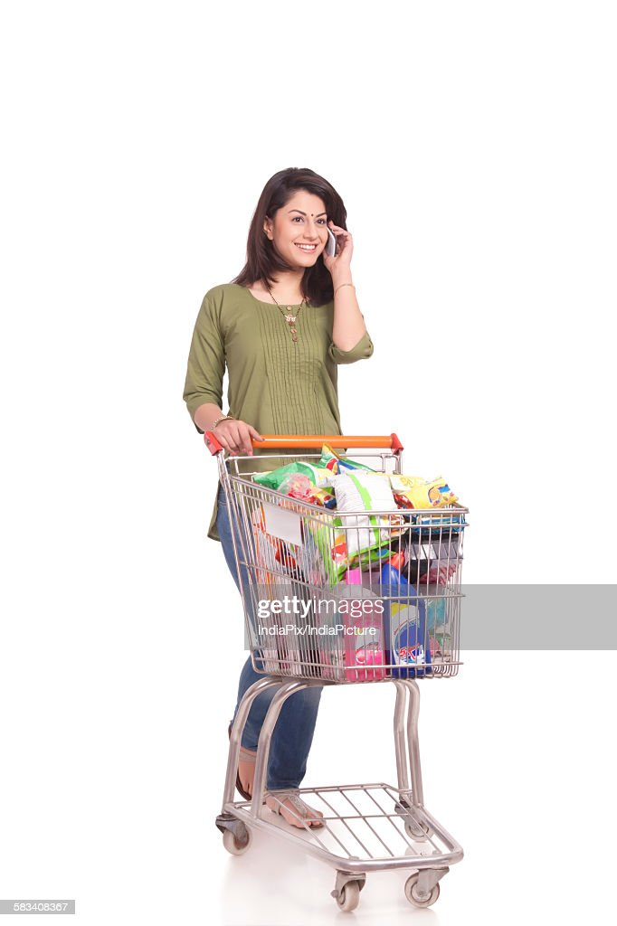 Married woman with shopping cart talking on mobile phone : Stock Photo