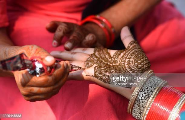 Married women applying Mehendi on the eve of Karva Chauth at Hanuman Mandir Cannaught Place on November 3, 2020 in New Delhi, India. Karwa Chauth...