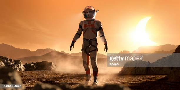 mars astronaut walking through rocky martian landscape during eclipse - mars stock pictures, royalty-free photos & images
