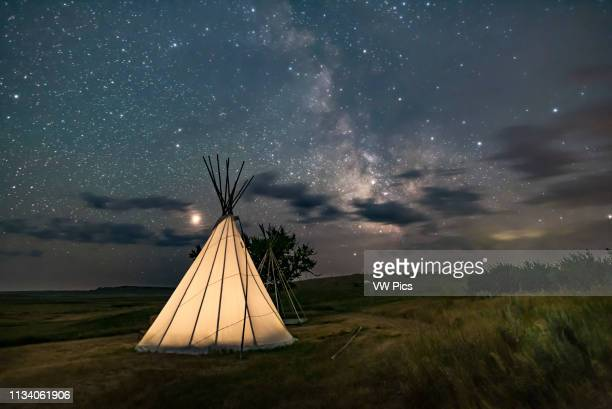 Mars at left and the Milky Way at right over a single tipi with another under construction at back at the Two Trees site at Grasslands National Park...