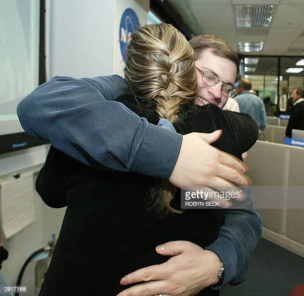 Mars Exploration Rover engineer Chris Voorhees hugs Jennifer Trosper Spirit's mission manager for surface operations as images of the empty...