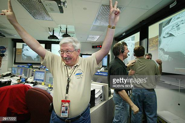 Mars Exploration Rover project manager Pete Theisinger and others in Mission Control react as images of the empty Opportunity rover lander arrive at...