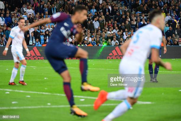 A Marseille fan shines a handheld laser onto the pitch during the Ligue 1 match between Olympique Marseille and Paris Saint Germain at Stade...