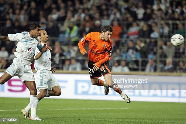 Lorient's forward AndrePierre Gignac vies with Marseille's defender Habib Beye and Garry Bocaly during the French L1 football match Marseille vs...