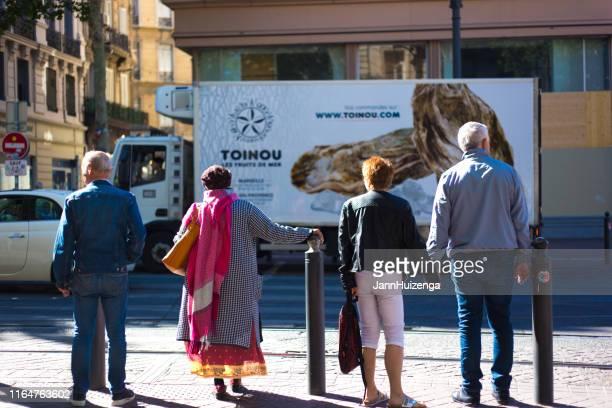 marseille, frankreich: fußgänger warten auf dasebiére - long dress stock-fotos und bilder