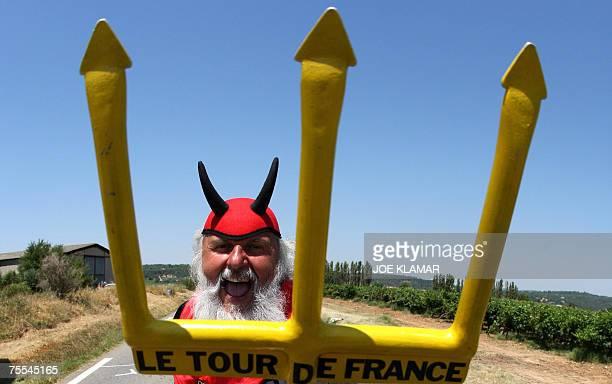 German fan Dieter Senft, known as El Diablo, poses with his devil costume in Saint-Maximin la-Sainte-Baume near Marseille as he waits for the riders...