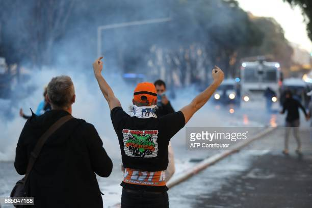 A Marseille supporter gestures during clashes with police a few hours prior to kick off of the French L1 football match between Marseille and Paris...