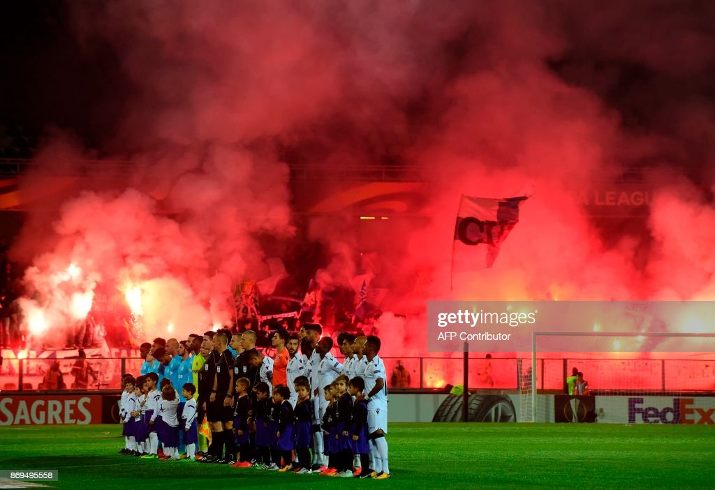 Marseille supporters light flares as players pose before the start of the UEFA Europa League group I football match Vitoria SC vs Marseille at the D. Afonso Henriques stadium in Guimaraes on November 2, 2017. /