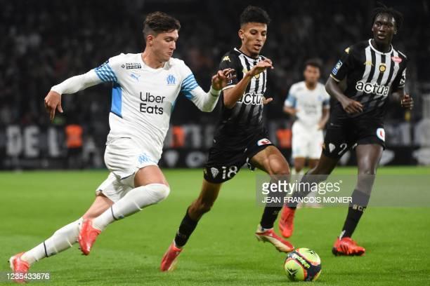 Marseille's Argentine defender Leonardo Balerdi fights for the ball with Angers' Morocan midfielder Azz-eddine Ounahi during the French L1 football...