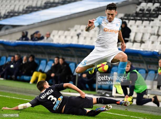 Marseille's Argentine midfielder Lucas Ocampos jumps over Bordeaux' Spanish defender Sergi Palencia during the French L1 football match between...