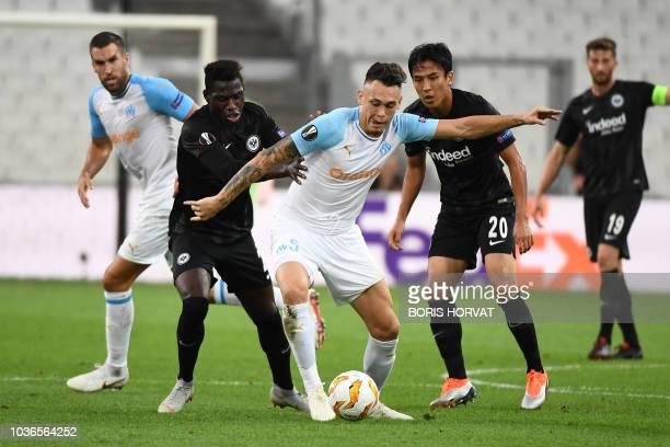 Marseille's Argentine midfielder Lucas Ocampos vies for the ball with Frankfurt's German defender Danny da Costa and Frankfurt's Japanese midfielder...