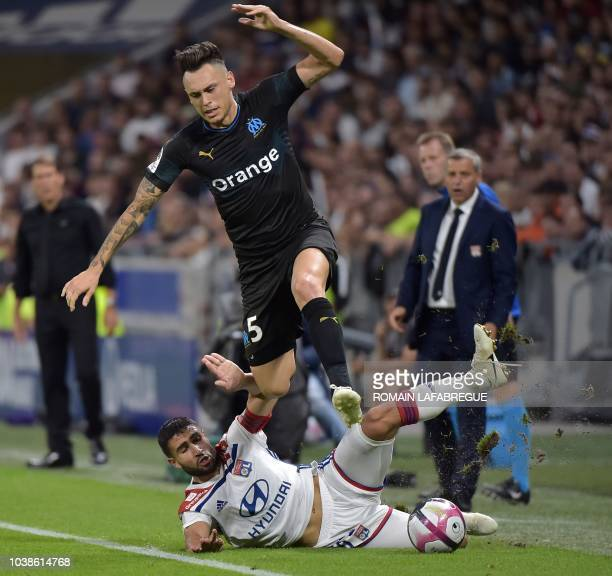 Marseille's Argentinian forward Lucas Ocampos is tackled by Lyon's French forward Nabil Fekir during the French L1 football match between Lyon and...