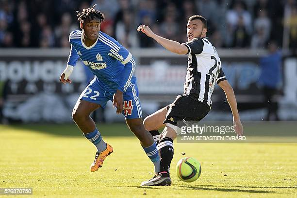 Marseille's Belgian forward Michy Batshuayi vies with Angers' Moroccan midfielder Romain Saiss during the French L1 football match between Angers and...