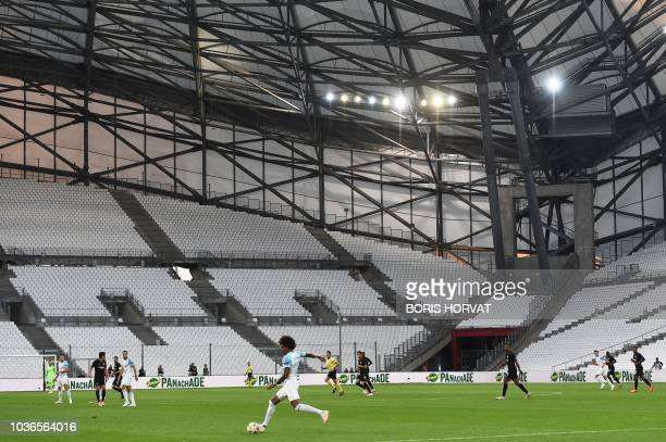 Marseille's Brazilian midfielder Luiz Gustavo runs with the ball in front of empty tribunes as the UEFA Europa League Group H firstleg football match...