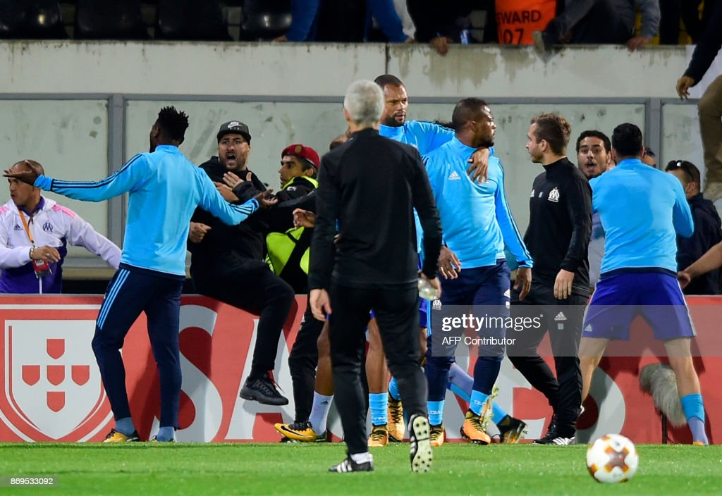 TOPSHOT - Marseille's defender Patrice Evra (C) leaves the pitch after an incident with Marseille supporters before the start of the UEFA Europa League group I football match Vitoria SC vs Marseille at the D. Afonso Henriques stadium in Guimaraes on November 2, 2017. /