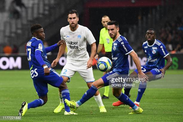 Marseille's Dutch midfielder Kevin Strootman fights for the ball with Strasbourg's French defender Kenny Lala and Strasbourg's French midfielder...