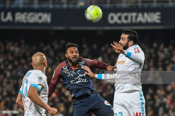 Marseille's French defender Adil Rami and Montpellier's Beninese midfielder Stephane Sessegnon go for a header during the French L1 football match...